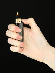 Burning lighter in female hand, isolated on black