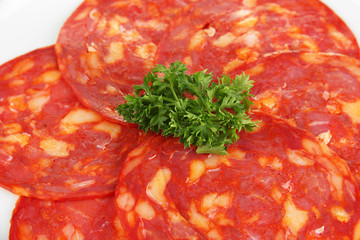 Salami slices on white plate, isolated on white