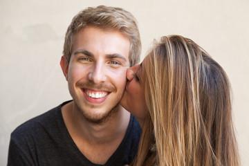 Coppia. Ragazza bacia il suo ragazzo sulla guancia