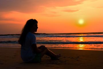 The silhouette ot girl sits on the beach. Enjoys a decline