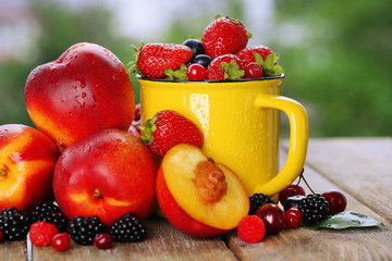 Peaches and berries on table on natural background