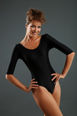 Funny girl in swimsuit on gray background