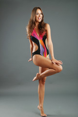 Beautiful woman with slim body in swimsuit on gray background