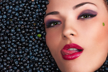 beautiful woman licking lips lying in blueberries
