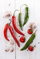 Colorful chilli peppers and species over white background