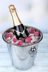 Frozen rose flowers in ice cubes and champagne bottle in