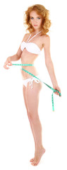 Beautiful young woman measuring her body with tape isolated