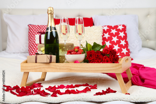 Romantic still life with champagne, strawberry and roses on bed