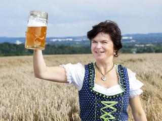 Bavarian woman in dirndl with beer mug in wheat field