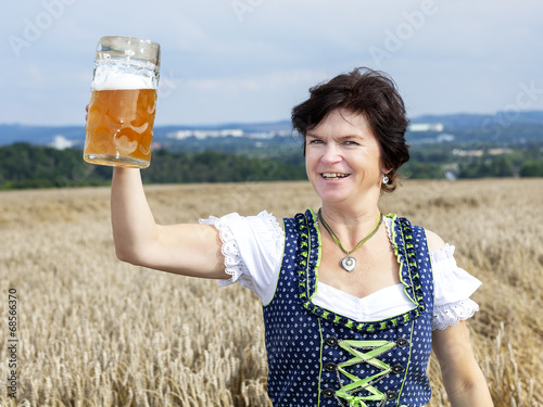 canvas print picture Bavarian woman in dirndl with beer mug in wheat field