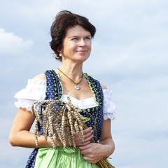 Bavarian woman in dirndl holds heads of grain in wheat field