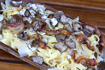 Pasta with truffles and bacon on a wooden plate