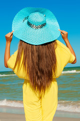 Beautiful girl with long hair on the beach in a blue hat