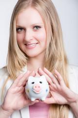 Mädchen zeigt ihr Sparschwein