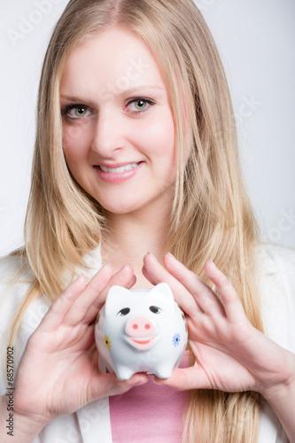 canvas print picture Mädchen zeigt ihr Sparschwein