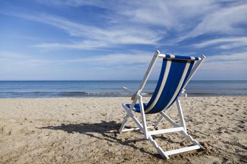 Bleu and white beach chair on the beach.