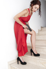 Beautiful  Woman with a red dress and a gun
