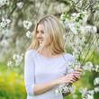 Obrazy na płótnie, fototapety, zdjęcia, fotoobrazy drukowane : Happy smiling woman in blooming garden in spring