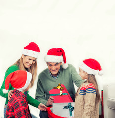 Happy family wearing red hats looking at Christmas gifts, isolat