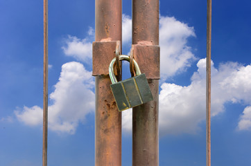 lock key on rusty fence and blue sky background