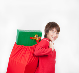 Happy kid carrying a bag full of Christmas gifts, isolated on wh