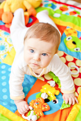 Infant boy on playmat