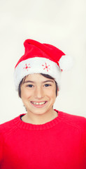 Happy smiling boy with red sweater and Christmas hat, isolated o