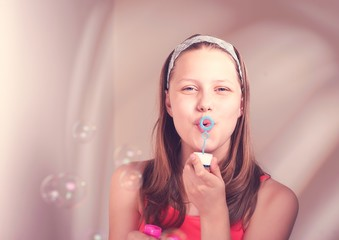 Happy teen girl blowing soap bubbles