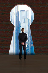 Businessman Looking At City Buildings Through Key Hole