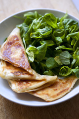 Cheese pancakes and green salad on a plate