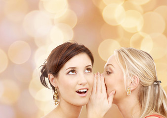 two smiling young women whispering gossip