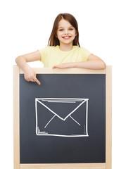 smiling little girl pointing finger to blackboard