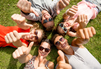 smiling friends showing thumbs up lying on grass