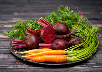 Beets and carrots on dark wooden background