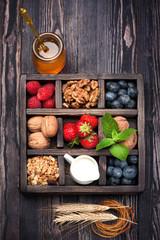 Breakfast  granola, nuts, berries, honey, milk in wooden box.