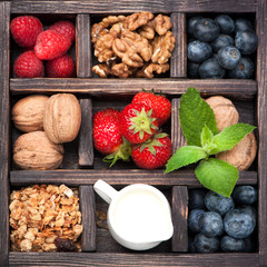 Granola, nuts, berries, milk in vintage box