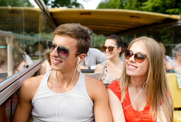 smiling couple with earphones traveling by bus