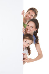Happy Family Peeking From Blank Billboard