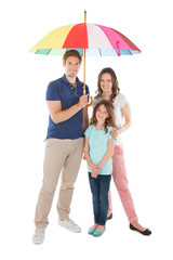 Portrait Of Family Standing Together Below Umbrella