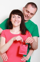 Man giving a gift to surprised smiling woman