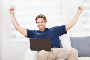 Excited Man With Laptop Raising Hands