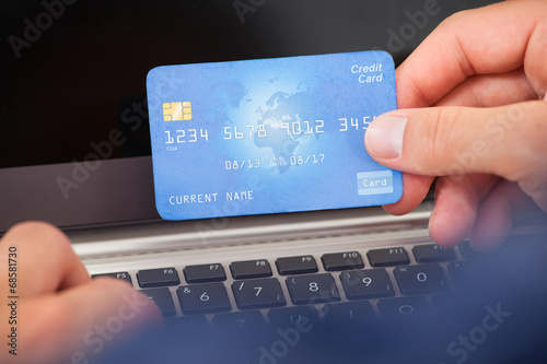 canvas print picture Man Using Credit Card And Laptop To Shop Online