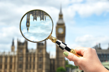 Magnifying glass in the hand against Big Ben in London