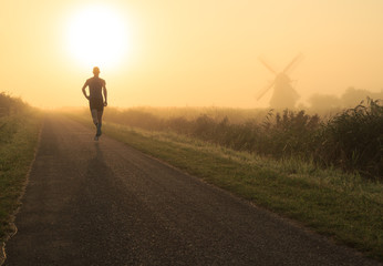 Man running in the foggy, Dutch countryside