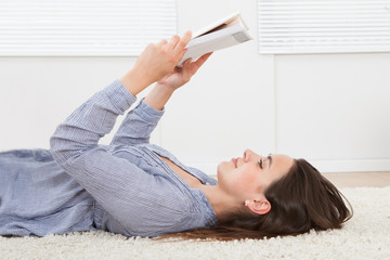 Woman Reading Book While Lying On Rug At Home