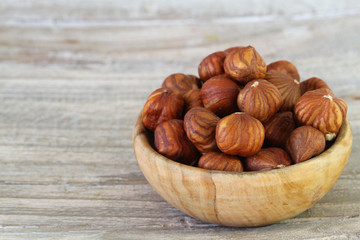 Hazelnuts without shell in wooden bowl with copy space