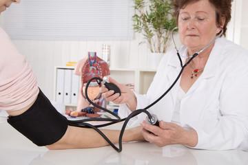 Ärztin misst den Blutdruck bei der Vorsorge