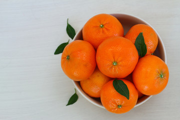 Mandarines in bowl on white wooden surface with copy space