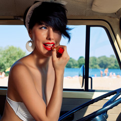 a beautiful retro-looking girl with blue eyes near the steering
