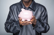 African american young man holding a piggy bank
